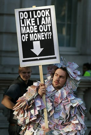 Students protest: A student holds a placard dressed in bank notes
