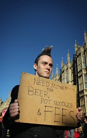 Students protest: Students hold placards as they march past the Houses of Parliament, London