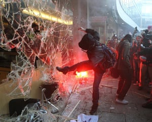 Students protest: A demonstrator kicks the windows of Millbank Tower, in Westminster
