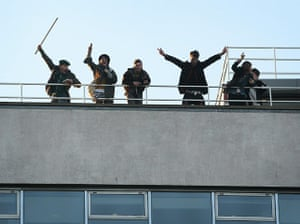 Students protest: Student protesters wave from the roof of Millbank