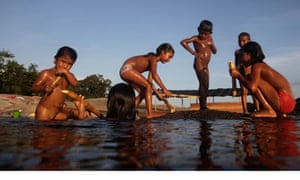 Children from Bare tribe play and eat sugar cane on the Negro River in northern Brazil