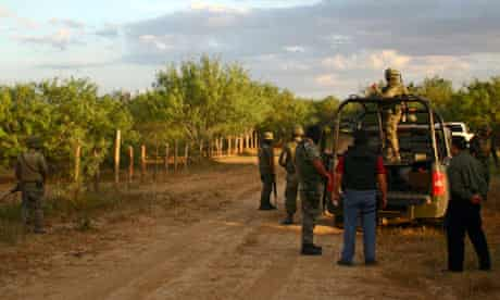 Army soldiers stop at a dirt road after a raid and gun battle on the vicinity of Ciudad Mier, Mexico