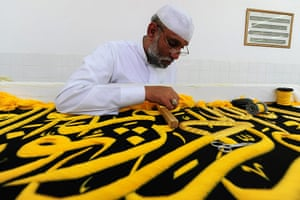 Hajj In Mecca: A Saudi worker sews Islamic calligraphy on a drape in Mecca