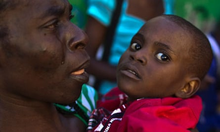 A woman carries a child with symptoms of cholera in Port-au-Prince
