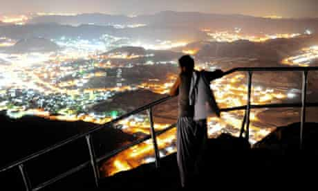 A hajj pilgrim looks at Mecca from the top of Noor mountain