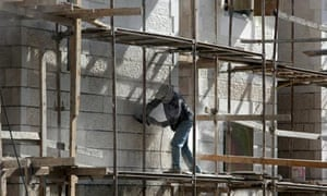 A Palestinian labourer works on Jewish settlement