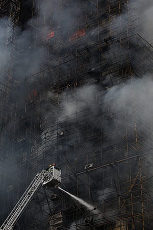 Shanghai fire: firefighters spray water as smoke pours from the building