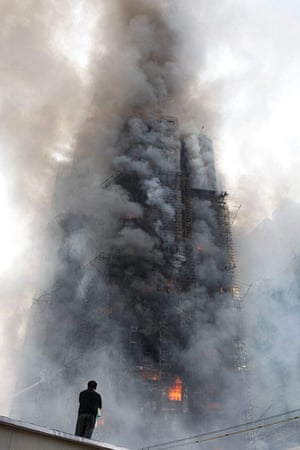 Shanghai fire: a Shanghai resident watches smoke pour from the building