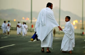 Hajj, Saudi Araba: A Muslim pilgrim walks with his son
