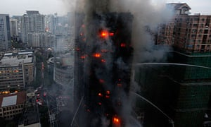Firefighters spray water on a burning block of flats in Shanghai