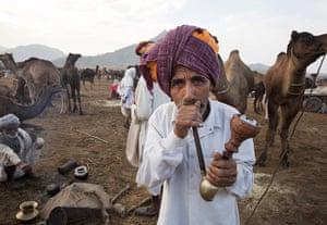 Pushkar camel fair: A fair-goer smokes a pipe