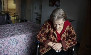 Elderly woman sits in her room at a nursing home, lost in thought.