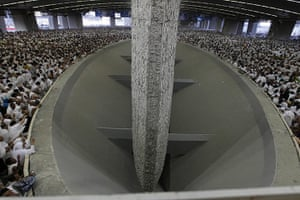 Hajj Pilgrimage: Muslim pilgrims cast stones at a pillar, symbolizing the stoning of Satan