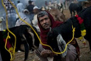 Eid al-Adha: An Indian Muslim feeds a sheep for sale