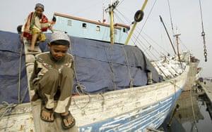 Eid al-Adha: Indonesian Muslim boys cross over a traditional ship
