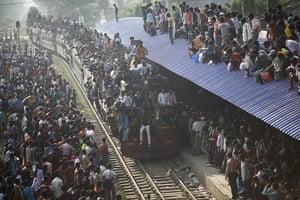 Eid al-Adha: An overcrowded train approaches a railway station in Dhaka