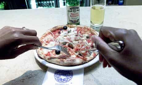 A customer eating a pizza at the London Wall branch of the Pizza Express restaurant chain.