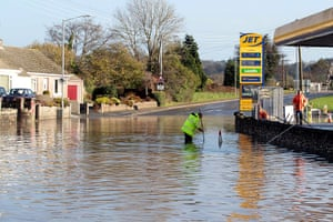 cornwall flooding: A garage worker tries to unblock a drain outside a garage in St Bazey