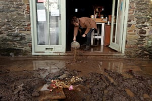 cornwall flooding: A woman bails water from her house in Lostwithiel