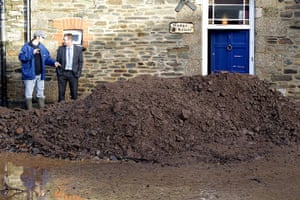 cornwall flooding: Residents look at the silt washed down a street in Lostwithiel
