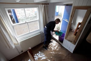 cornwall flooding: Jane Hurd bails water from her flooded house in Lostwithiel