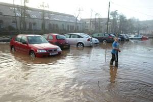 cornwall flooding: Early morning walker navigate flood water in Lostwithiel