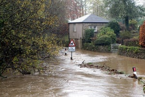 cornwall flooding: Flood water gushes down a road outside Lostwithiel