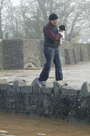 cornwall flooding: A woman carries her dog over a wall in St Austell