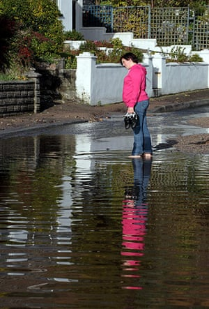 cornwall flooding: A woman looks at a flooded road in St Bazey