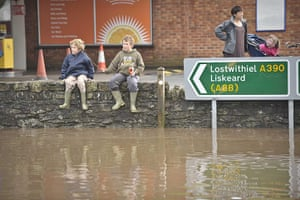 cornwall flooding update: Children in wellington boots sit on a wall and play in St Blazey,