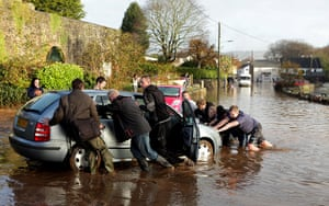 cornwall flooding update: Residents move a car stranded in flood water in St Blazey
