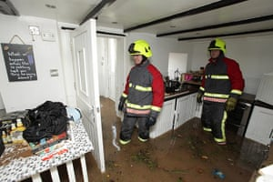 cornwall flooding update: Firemen clear a flooded house in St Blazey