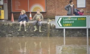 Children dressed in wellington boots sit on a wall and play in St Blazey