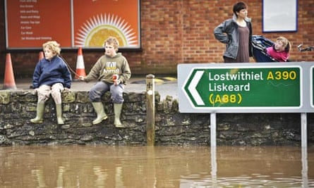 Children sit on a wall above floodwater in St Blazey, Cornwall