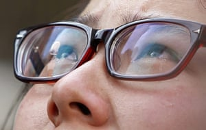 Shanghai Memorial: A woman weeps as she looks at the entrance of a burnt apartment block