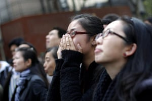 Shanghai Memorial: People react as they look on at the entrance of a burnt apartment block