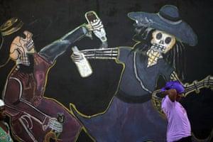 All Saints: Port-au-Prince, Haiti: A woman stands by a mural