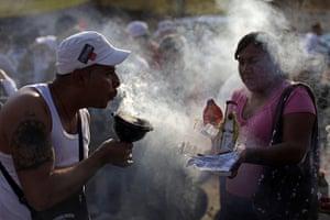 All Saints: A man blows incense smoke at a couple of Santa Muerte