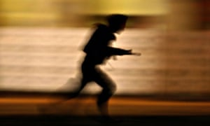 An Indian soldier runs to take a position in Mumbai during the November attack
