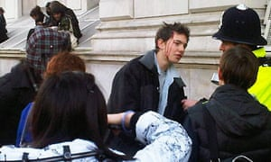 A student protester bleeds from the head during demonstrations in central London