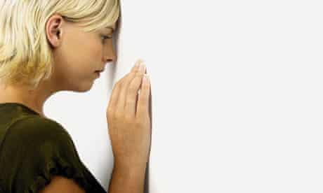 Depressed woman facing wall