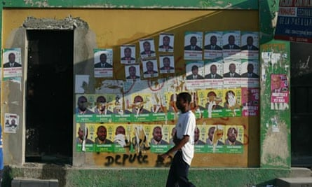 A Haitian walks before campaign posters