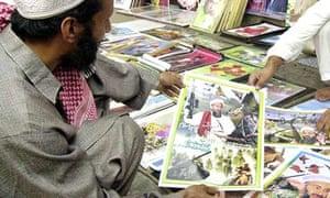 Pakistani men look at posters depicting Osama bin Laden as a hero at a roadside shop in Peshawar