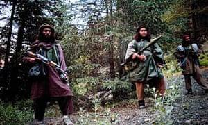 Haqqani Taliban fighters carrying guns in their mountain camp