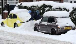Snow and freezing hits uk: A man digs his car out in Monkseaton