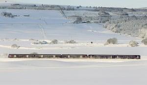 Snow and freezing hits uk: A passenger train makes its way past Greenloaning