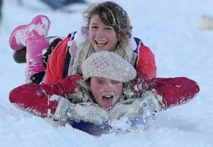 Snow and freezing hits uk: Rachel Douglass and Sophie Coatsworth sledge downhill