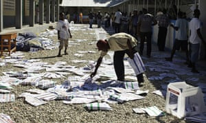 Haiti Elections: man picks up ballots after frustrated voters destroyed electoral material