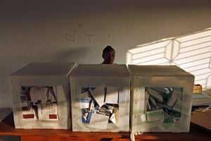 Haiti Elections: An electoral worker waits behind ballot boxes