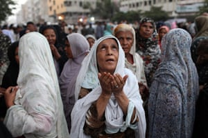 Karachi Pakistan: Women offer prayers at a rally held by the Lyari Aman (Peace) Committee